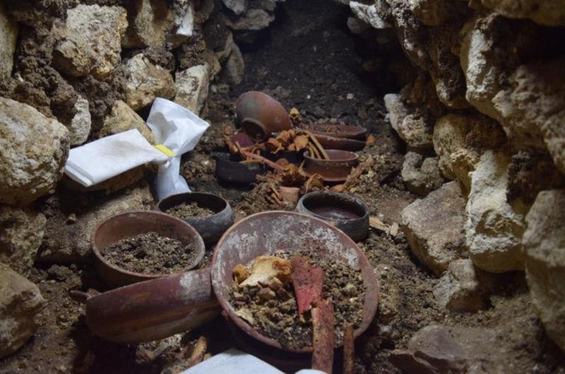 Enterramiento 80. La excavación muestra una taza de piedra en el centro rodeada por los huesos.