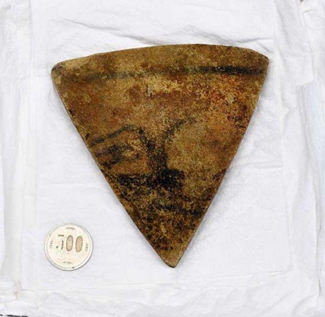 Una pieza de piedra con la pintura de un rostro humano y encontrada en Kikonai, Hokkaido.
