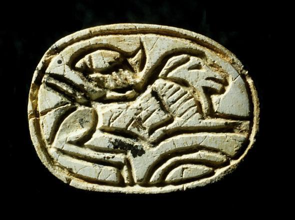 El escarabajo egipcio encontrado en el cofre de la niña representa un león agazapado y el sol saliendo por una colina