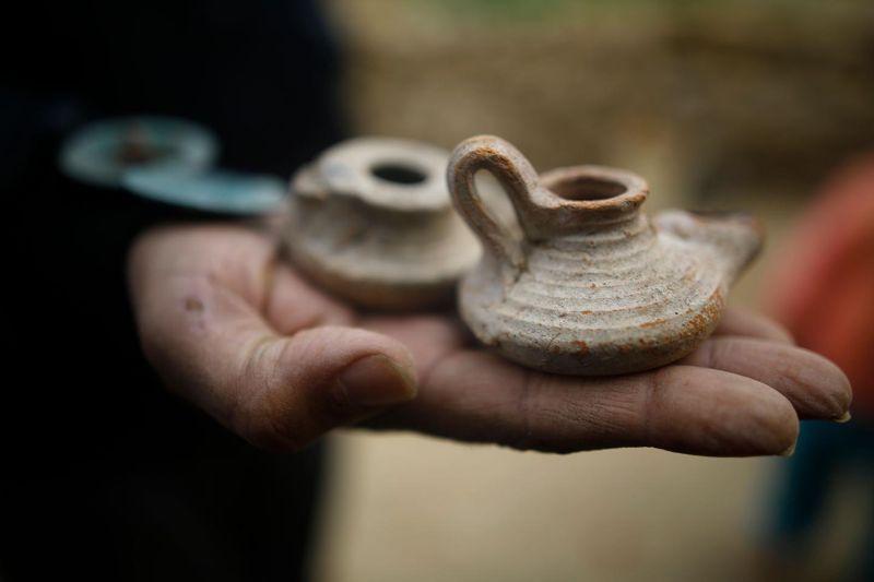 Una foto tomada el 26 de enero de 2018 muestra objetos pequeños de cerámica encontrados en un cementerio recientemente descubierto en el jardín de una casa en Beit Hanun. Los expertos dijeron que las tumbas eran parte de una tumba loculus que posiblemente data de la época romana-bizantina tardía en el cuarto al sexto siglo d.C