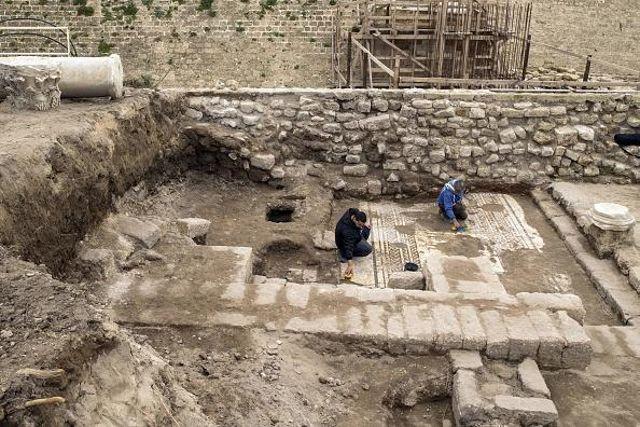 Trabajadores de la Autoridad de Antigüedades de Israel limpiando el mosaico. Este mide aproximadamente 11.5 pies de ancho y 26 pies de largo y representa a tres hombres vestidos de toga, que parecen representar a los miembros de la clase alta