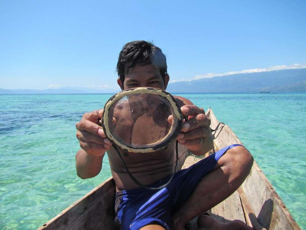Un buzo de Bajau que muestra una máscara de buceo de madera tradicional