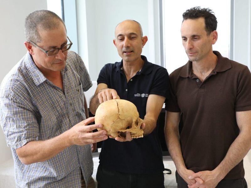 De izquierda a derecha: Prof. Boaz Zissu, Dr. Yossi Nagar y Dr. Haim Cohen con el cráneo de 1.000 años