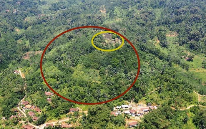 La estructura en forma de pirámide permaneció oculta durante tanto tiempo porque ha sido ocultada por el follaje y, por lo tanto, parece una colina (círculo rojo), con un megalito expuesto en la parte superior (círculo amarillo)