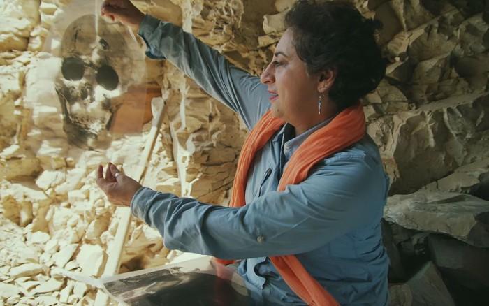La arqueóloga Salima Ikram examina una imagen de un cráneo del entierro masivo